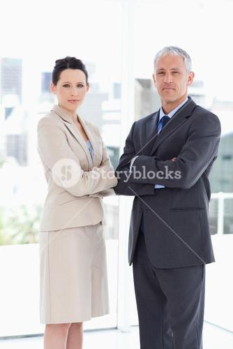 Young businesswoman standing upright with her mature director