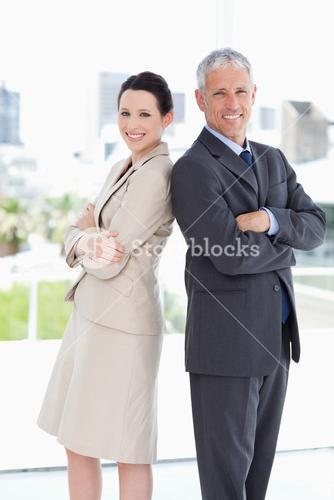 Smiling business people looking at the camera while standing upright