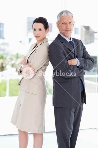 Two serious business people standing in a bright room