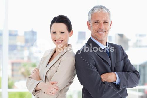 Mature businessman and his secretary standing upright side by side