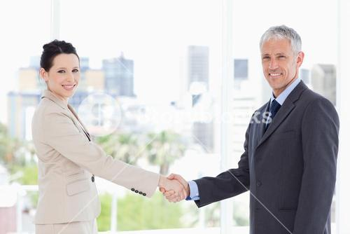Smiling business people shaking hands while looking at the camera