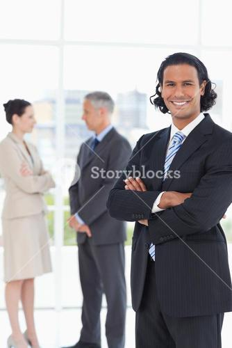 Young smiling executive standing upright in front of two business people