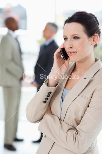 Businesswoman seriously talking on the phone with executives behind her