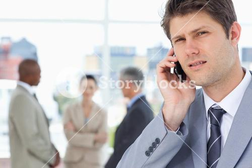 Serious executive looking straight ahead while using a mobile phone