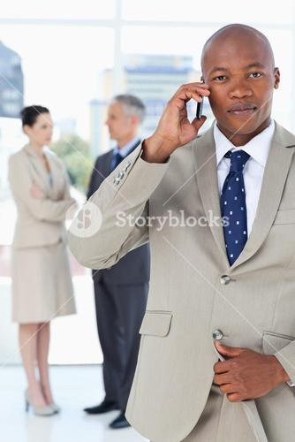 Young manager talking on the phone very seriously while his team stands behind him