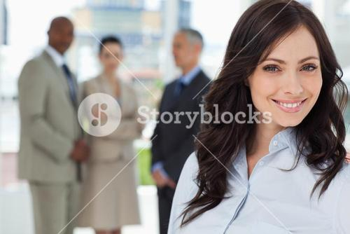 Young executive woman smiling and looking ahead with the team in the background