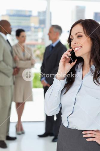 Young executive woman talking on the phone with one hand on her hip
