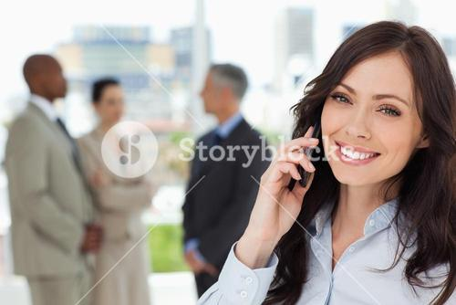 Young smiling businesswoman on the phone and tilting her head to one side
