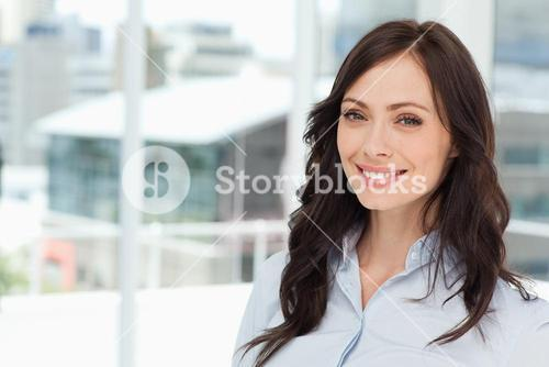 Young smiling executive woman standing upright in front of the window