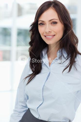 Young smiling manager standing upright in front of the bright window