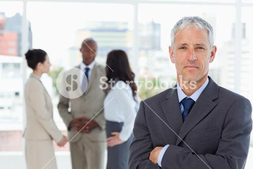 Serious businessman crossing his arms while his team is in the background