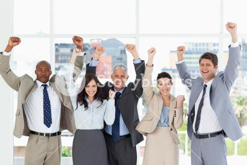 Smiling business team standing upright with arms raised in success