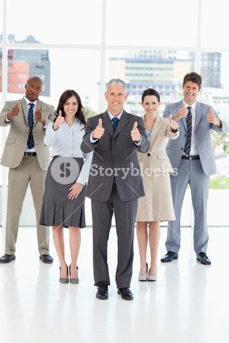 Business team standing together with their thumbs up in success