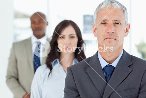 Mature and serious manager standing upright and followed by two employees