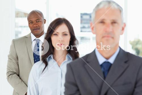 Young and serious businessman following two members of his team