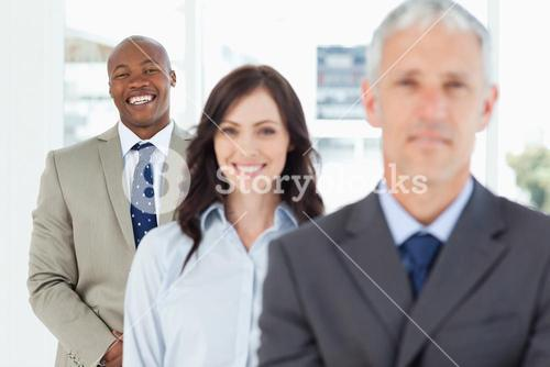 Young smiling employee standing upright and following his team