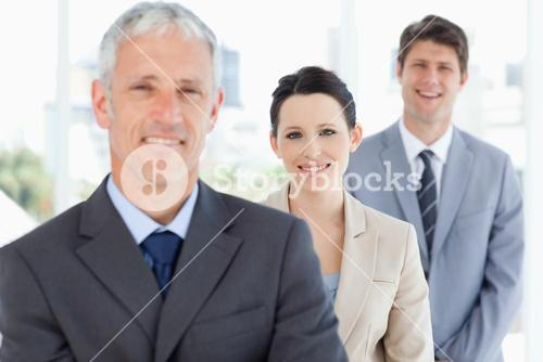 Young smiling executive woman wearing a formal suit between two businessmen