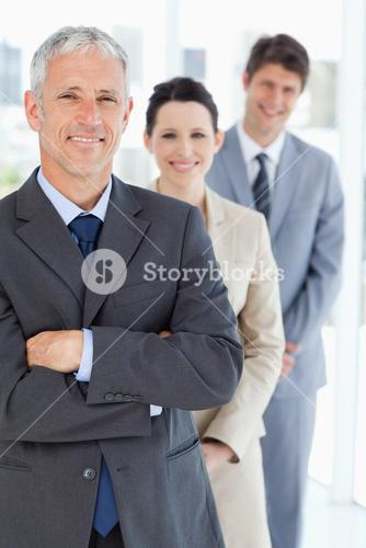 Smiling mature businessman standing upright in front of his young team