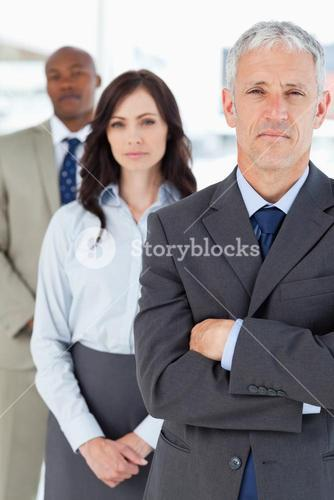 Mature manager crossing his arms seriously in front of two members of his team