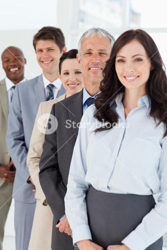 Confident and smiling manager standing among his employees