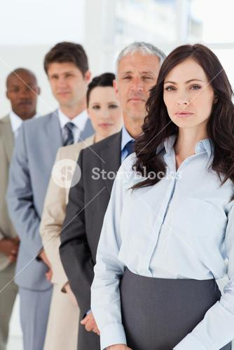 Serious executive woman standing upright in front of her business team