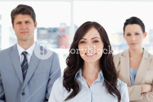 Young smiling woman standing in front of two coworkers