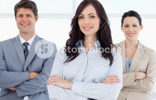 Young smiling executive woman crossing her arms in front of two colleagues