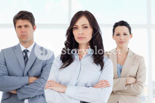 Three serious business people crossing their arms in a welllit room