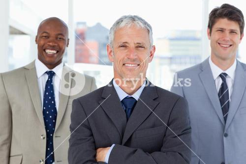 Mature director standing upright in front of his two smiling executives