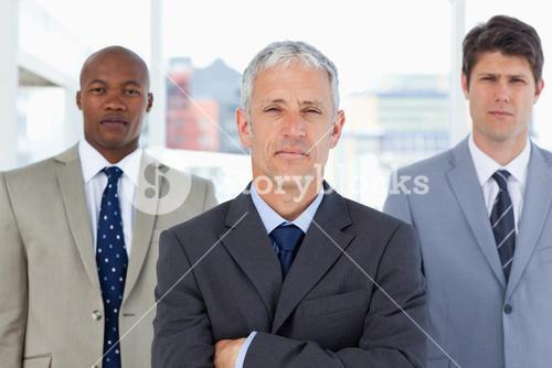 Serious mature manager standing in front of his two executives