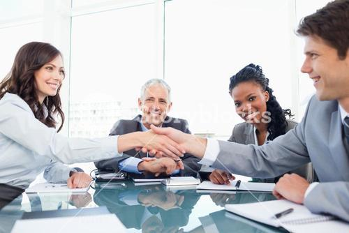 Two young executives shaking hands in front of their director and a colleague
