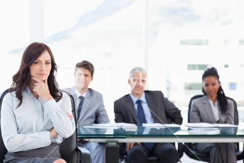 Young executive woman almost smiling with her hand on her chin in a meeting room