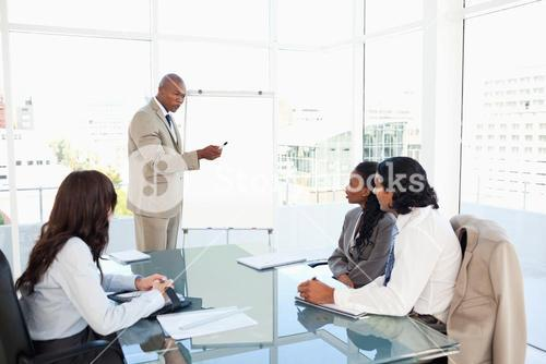 Businessman pointing to something on the flipchart to explain this to his colleagues