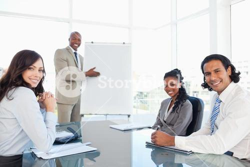 Smiling executive showing a flipchart while his colleagues are listening to him