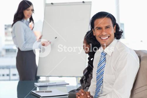 Young employee smiling during a presentation while his team is working behind him