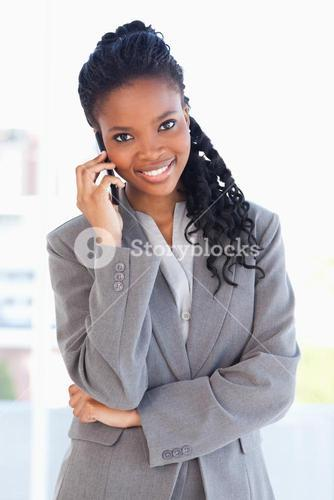 Young smiling employee standing upright and talking on a phone with her arms crossed