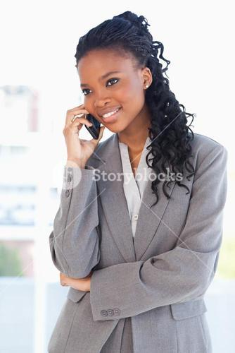 Young smiling executive woman crossing her arms while talking on a phone