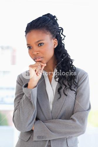 Businesswoman looking towards the side with her hand on her chin in a bright room