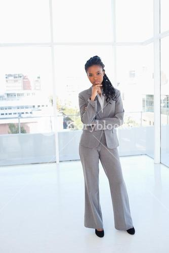 Young earnest businesswoman standing in front of a bright window