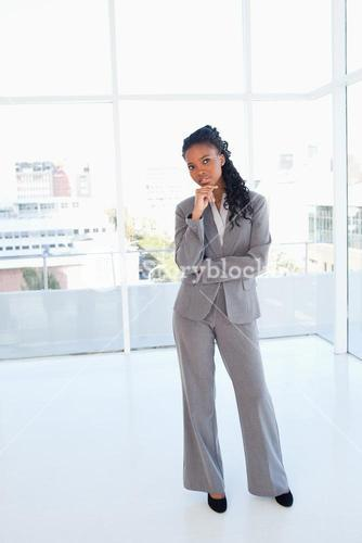 Businesswoman standing upright with her hand on her chin and with her arms crossed
