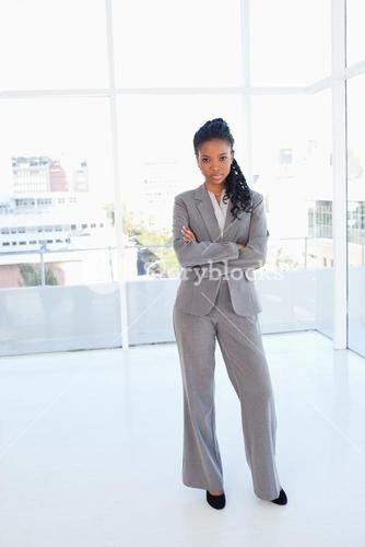 Serious secretary standing upright while crossing her arms
