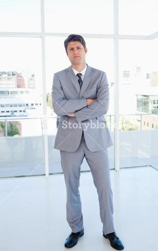 Businessman standing upright in front of a bright window and crossing his arms