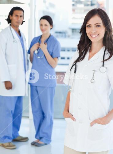 Smiling female doctor standing upright with her hands in her pockets
