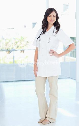 Young smiling nurse standing upright with one hand on her hip