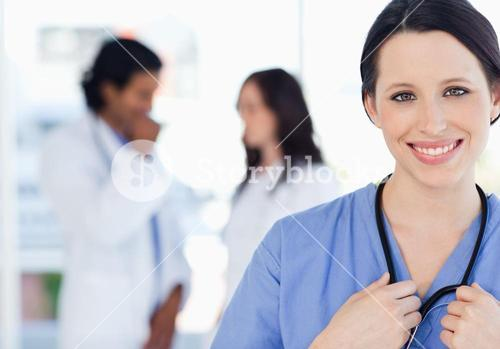 Confident nurse standing upright accompanied by her team in the background
