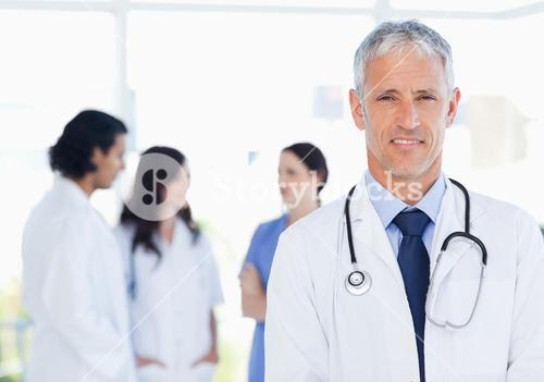 Mature and calm doctor standing upright in front of his medical interns