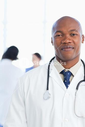 Young and confident doctor grinning in front of his medical team