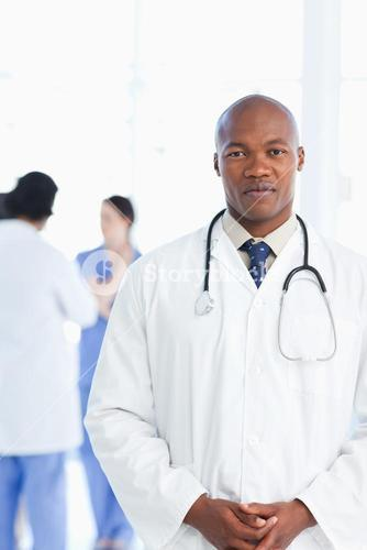 Doctor standing upright with his hands crossed and his team in the background