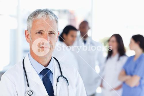 Mature doctor looking straight ahead while his team is looking at him