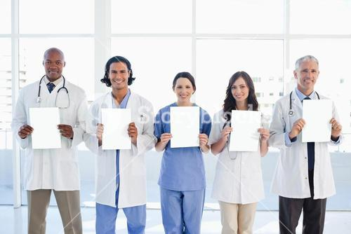 Medical team standing upright in front of the window while showing blank sheets
